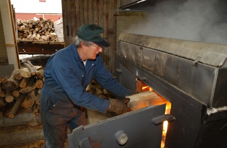 Feeding the evaporator fire at a sugar house in Cambridge, Vermont