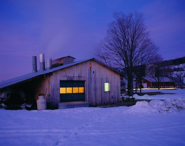 Boiling maple syrup at the sugar shack at dusk in Ira, Vermont