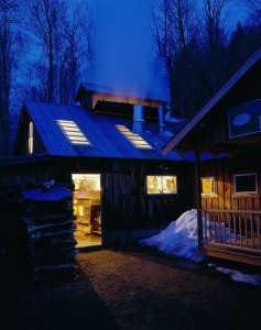 Boiling maple syrup in the sugar shack at dusk in Elmore, Vermont