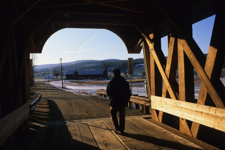 Man walking under a covered bridge on a country road with a farm on the horizon in Coventry, Vermont.