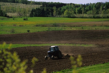 Spring Farmer raking his farm field with scenic field view in background in Shoreham, Vermont.