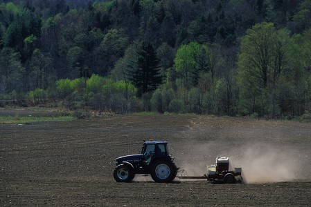 Spring Farmer uses his tractor to seed his farm field in Hyde Park, Vermont
