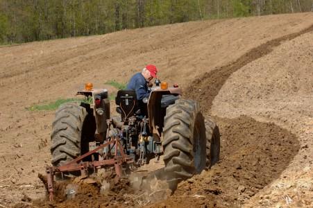 A Bakersfield, Vermont farmer plowing his fields.