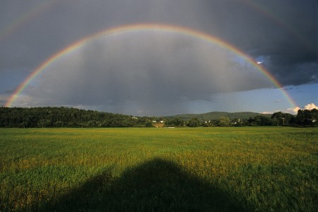 Rainbows stretch over a field during a rainstorm in Canaan, Vermont