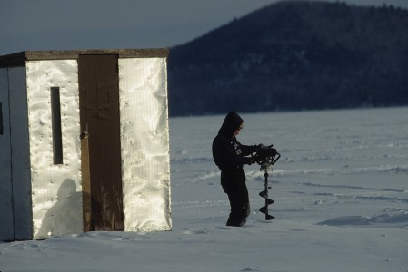 Fisherman at The Annual Islands Ice Fishing Derby with a hole saw on Lake Champlain in South Hero, Vermont.
