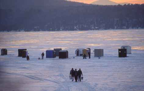 Ice Fisherman on Lake Champlain in Charlotte, Vermont With the Adirondack Mountains of NewYork in the background.