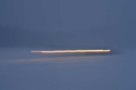Art photo of car on frozen Lake Champlain time exposure at dusk in Shelburne, Vermont.