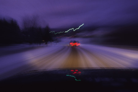 Time exposure of cars at dusk driving down country road in Underhill, Vermont snowstorm.
