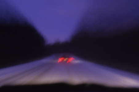 Time exposure of cars at dusk driving down country road in Williston, Vermont snowstorm.