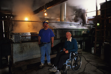 Sugar maker standing by the evaporator with a man at his sugar house in Morse Farm in Montpelier, Vermont